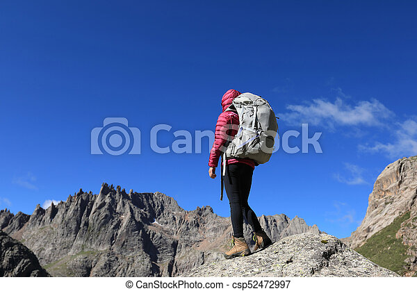woman with backpack hiking in mountains - csp52472997