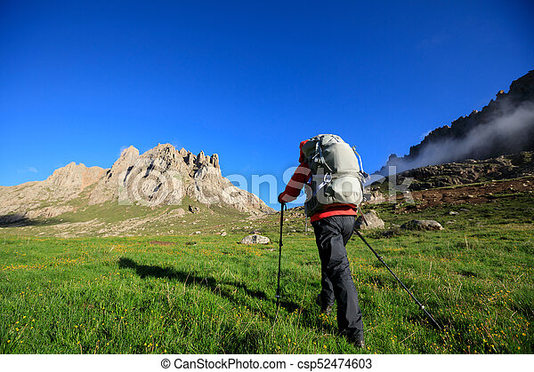 woman with backpack hiking in mountains travel lifestyle - csp52474603