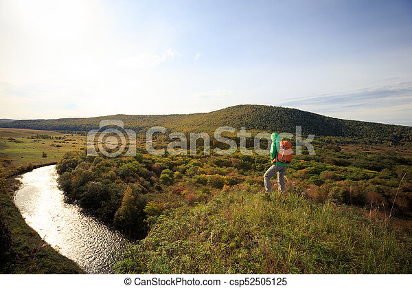 woman with backpack hiking in the autumn forest - csp52505125