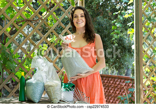 Woman with fertilizer granules in bag  - csp22974533