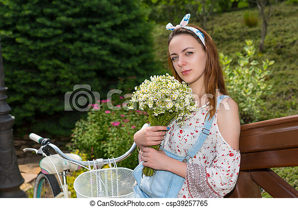 Woman with flowers standing near bike - csp39257765