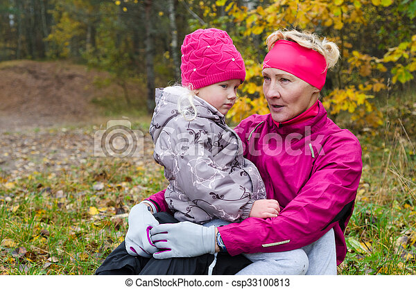 Woman with girl doing aerobics in the autumn park - csp33100813