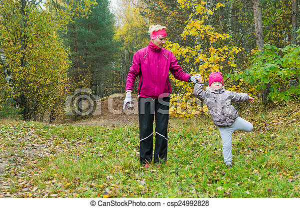 Woman with girl doing aerobics in the autumn park - csp24992828