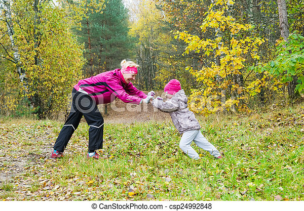 Woman with girl doing aerobics in the autumn park - csp24992848