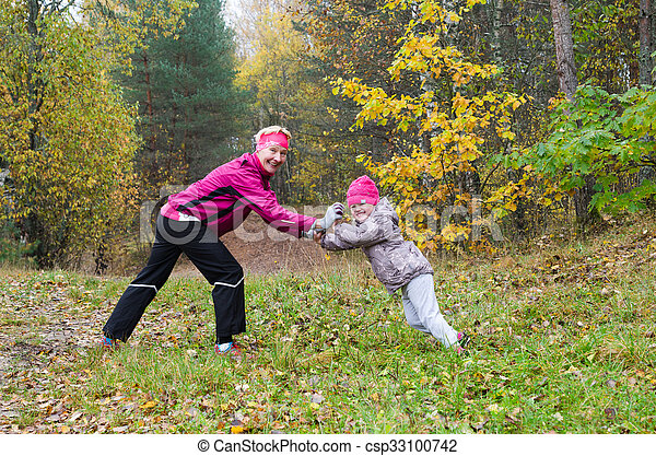 Woman with girl doing aerobics in the autumn park - csp33100742