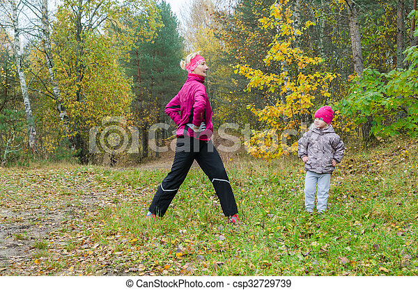 Woman with girl doing aerobics in the park - csp32729739