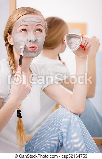 Woman with grey clay mud mask on her face - csp52164753
