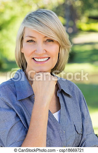 Woman with hand on chin in park - csp18669721
