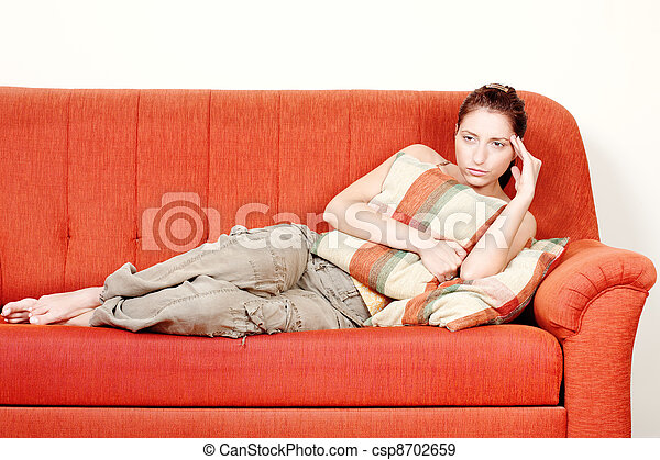 Woman with headache laying on sofa at home - csp8702659