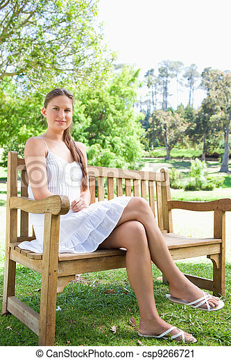 Woman With Her Legs Crossed Sitting On A Park Bench Young Woman