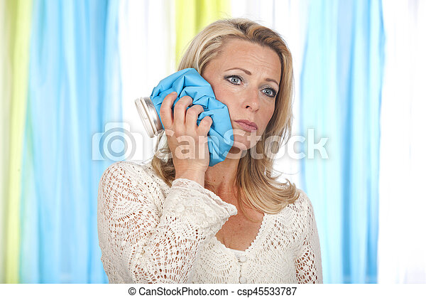 Woman with ice pack on her cheek - csp45533787