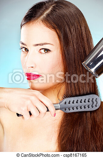 woman with long hair holding blow dryer and comb - csp8167165
