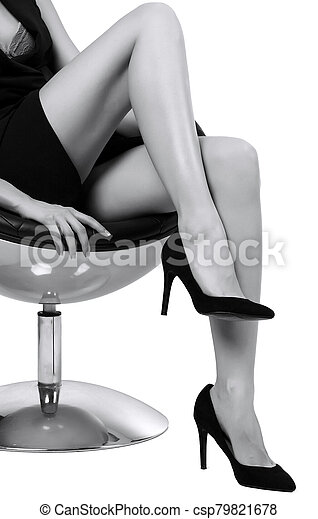Woman with long legs sitting in a chair, isolated on white background - csp79821678