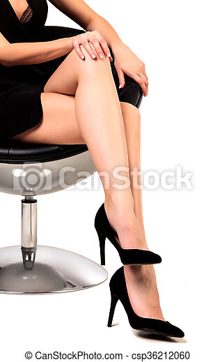 Woman with long legs sitting in a chair, isolated on white background - csp36212060