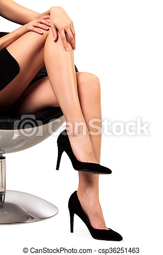 Woman with long legs sitting in a chair, isolated on white background - csp36251463