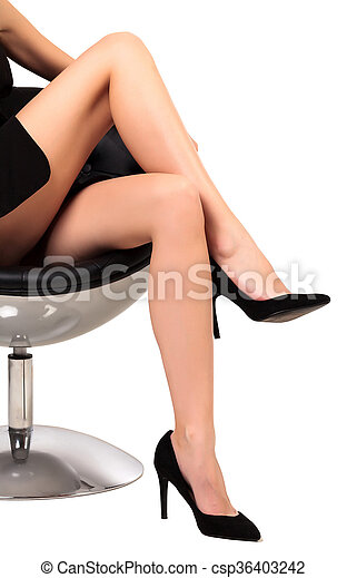 Woman with long legs sitting in a chair, isolated on white background - csp36403242