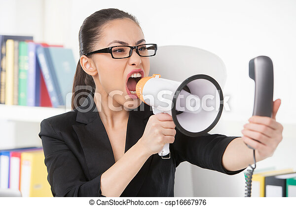 Woman with megaphone. Angry young businesswoman shouting at megaphone while talking on the phone - csp16667976