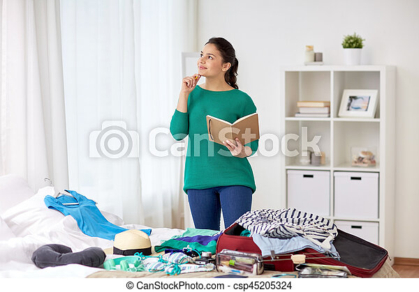 woman with notebook planning her trip at home - csp45205324