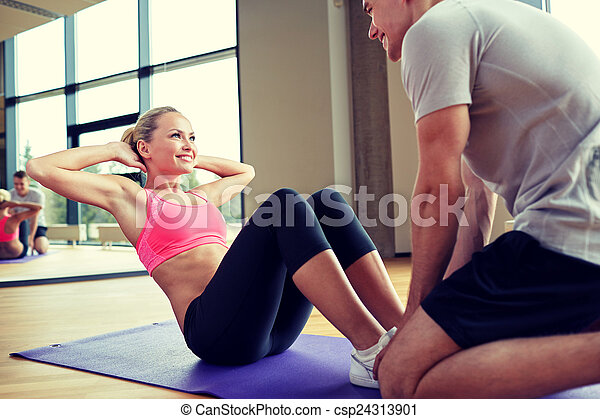 woman with personal trainer doing sit ups in gym - csp24313901