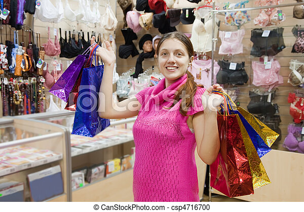 f2f41f4c0 Woman with purchases in underwear shop. Happy woman with purchases ...