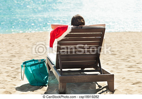 a47235908eb Woman with Santa hat relaxing on deck chair at beach resort - csp18919282
