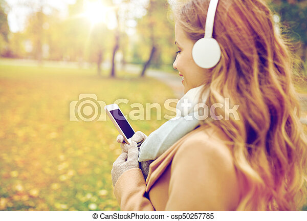 woman with smartphone and earphones in autumn park - csp50257785