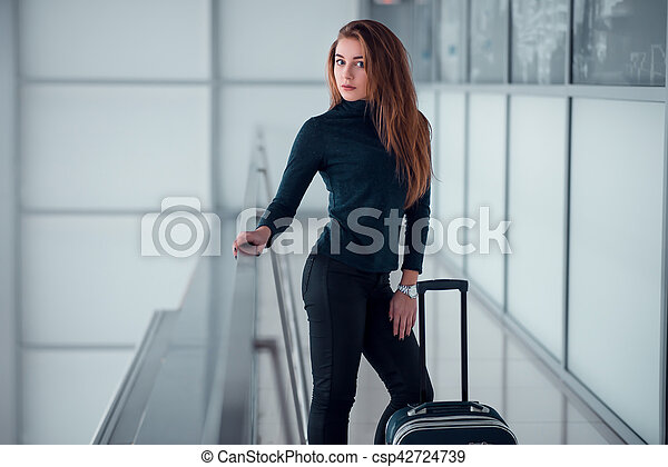 Woman with suitcase posing on the glassed balcony. - csp42724739