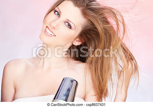 woman with towel holding blow dryer - csp8637431