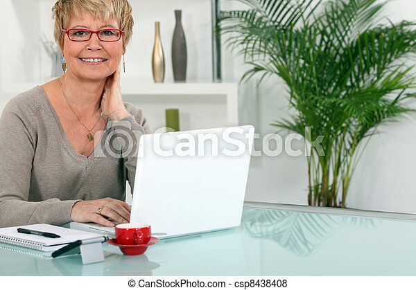Woman working on her laptop at home - csp8438408