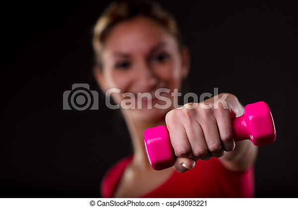 Woman working out with a colorful dumbbell - csp43093221