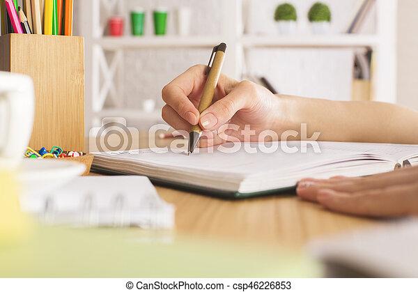 Woman writing in copybook - csp46226853