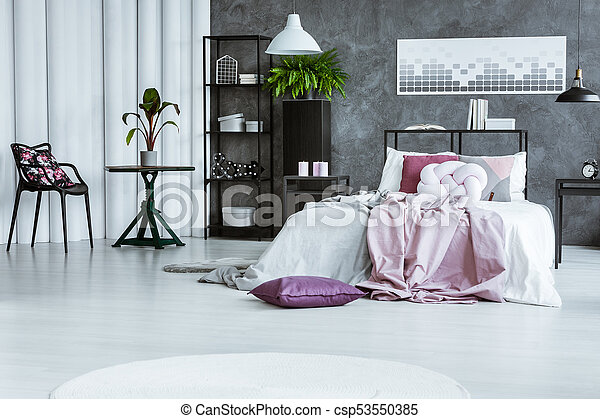 Woman\'s bedroom with black chair