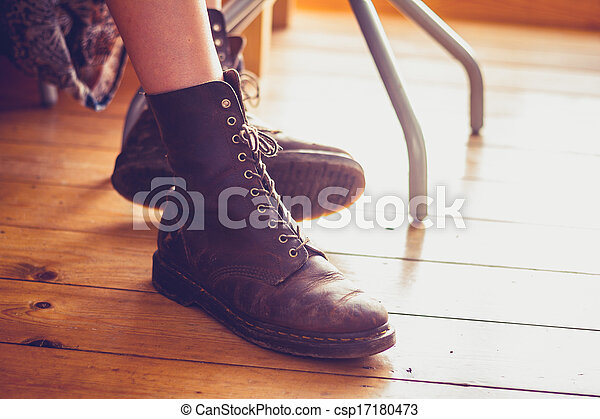 Woman's feet in leather boots on wooden floor - csp17180473