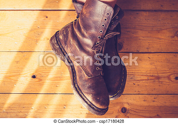 Woman's feet in leather boots on wooden floor - csp17180428