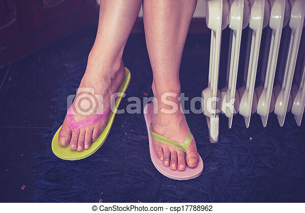 Woman's feet in sandals next to radiator - csp17788962