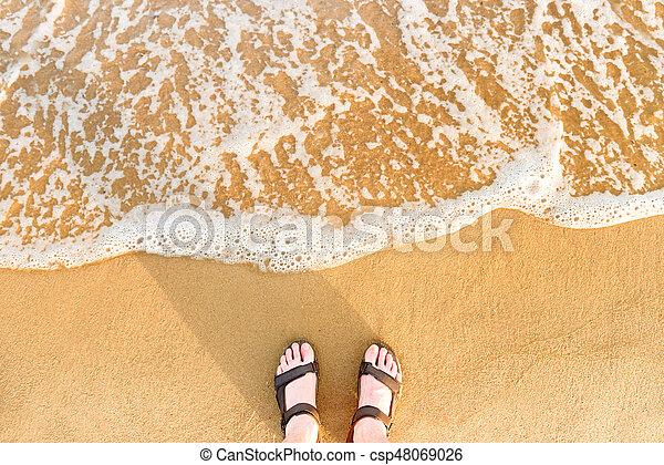 Woman's feet in sandals on a beach sand - csp48069026