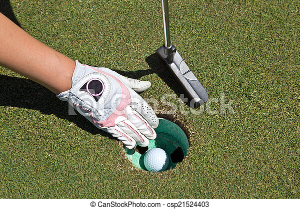 Woman's gloved hand, putter and golf ball in the cup - csp21524403