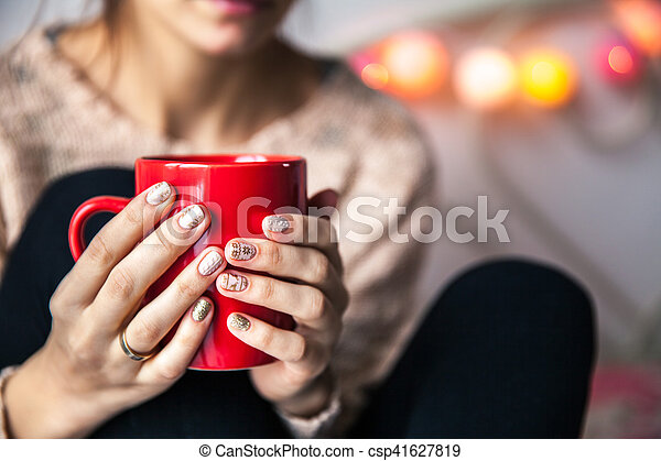 Woman's hand holding a red cup of coffee. With a beautiful winter manicure. Drink, fashion, morning - csp41627819