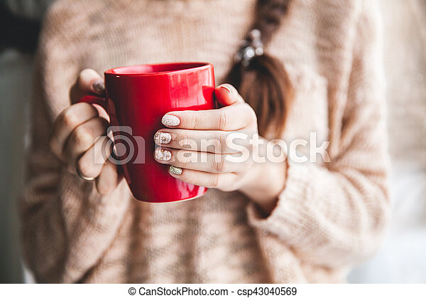 Woman's hand holding a red cup of coffee. With a beautiful winter manicure. Drink, fashion, morning - csp43040569