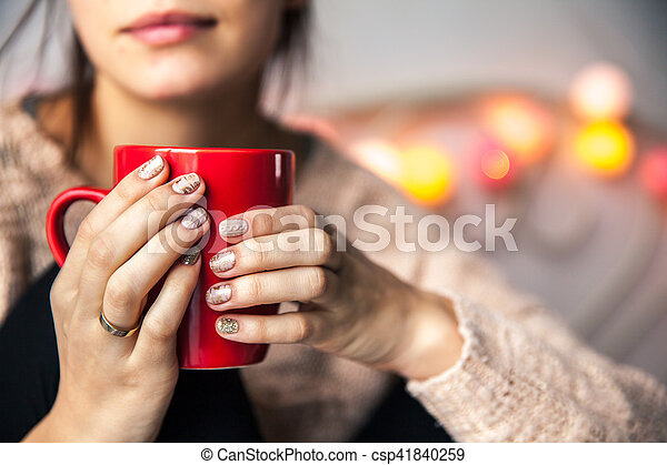 Woman's hand holding a red cup of coffee. With a beautiful winter manicure. Drink, fashion, morning - csp41840259