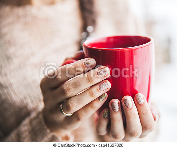 Woman's hand holding a red cup of coffee. With a beautiful winter manicure. Drink, fashion, morning - csp41627820