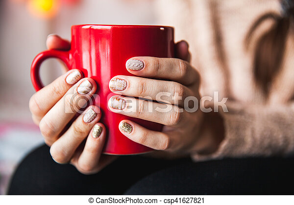 Woman's hand holding a red cup of coffee. With a beautiful winter manicure. Drink, fashion, morning - csp41627821