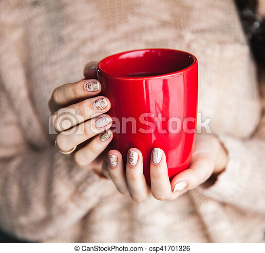 Woman's hand holding a red cup of coffee. With a beautiful winter manicure. Drink, fashion, morning - csp41701326