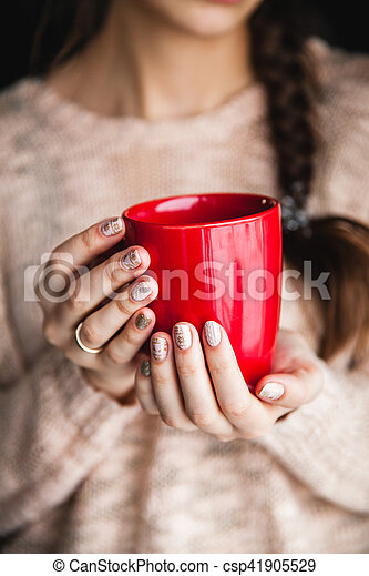 Woman's hand holding a red cup of coffee. With a beautiful winter manicure. Drink, fashion, morning - csp41905529