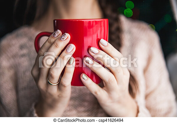 Woman's hand holding a red cup of coffee. With a beautiful winter manicure. Drink, fashion, morning - csp41626494