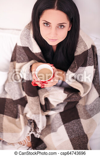 Woman's hand holding a red cup of coffee. With a beautiful winter manicure. Drink, fashion, morning - csp64743696
