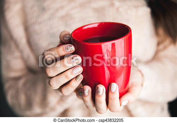 Woman's hand holding a red cup of coffee. With a beautiful winter manicure. Drink, fashion, morning - csp43832205