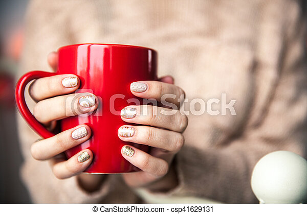 Woman's hand holding a red cup of coffee. With a beautiful winter manicure. Drink, fashion, morning - csp41629131