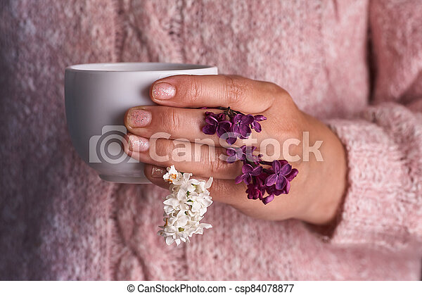 Woman's hand holding a white cup of coffee. With a beautiful lilac flowers. Drink, fashion, morning - csp84078877