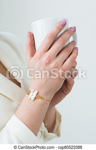 Woman's hand holding a white cup of coffee. With a beautiful manicure close-up. Drink, fashion, morning - csp80523388